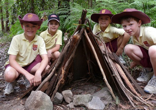 A group of student crouching beside an Aboriginal gunyas.